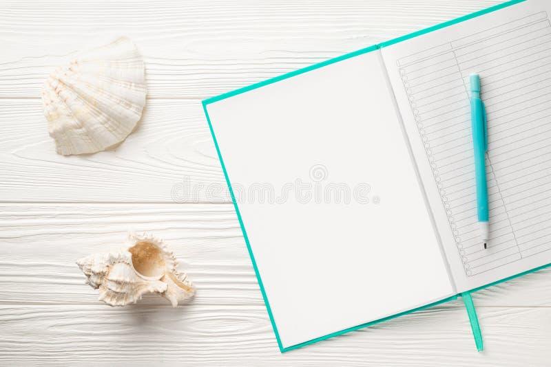 Blanc de bloc-notes et crayon automatique sur une table en bois blanche avec des coquilles image stock