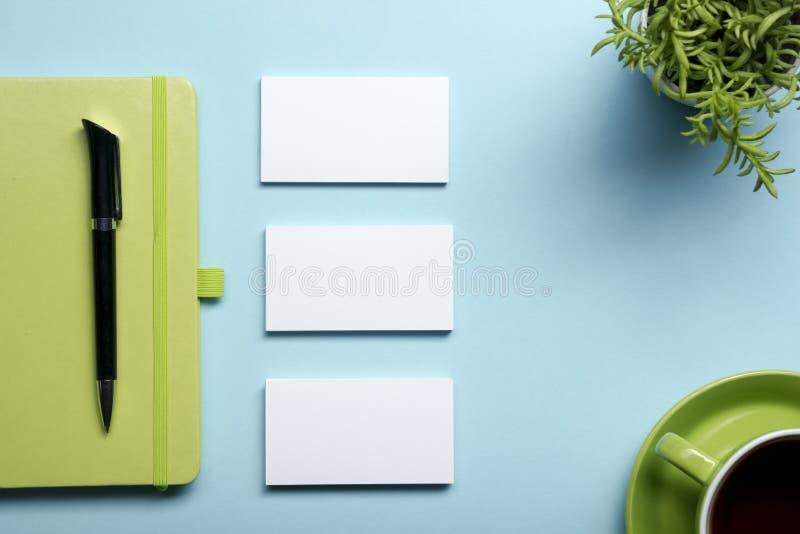 Blanc de carte de visite professionnelle de visite, bloc-notes, fleur, tasse de café et stylo à la vue supérieure de table de bur image stock