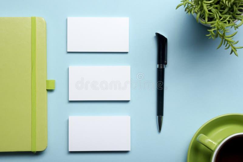 Blanc de carte de visite professionnelle de visite, bloc-notes, fleur, tasse de café et stylo à la vue supérieure de table de bur photos libres de droits