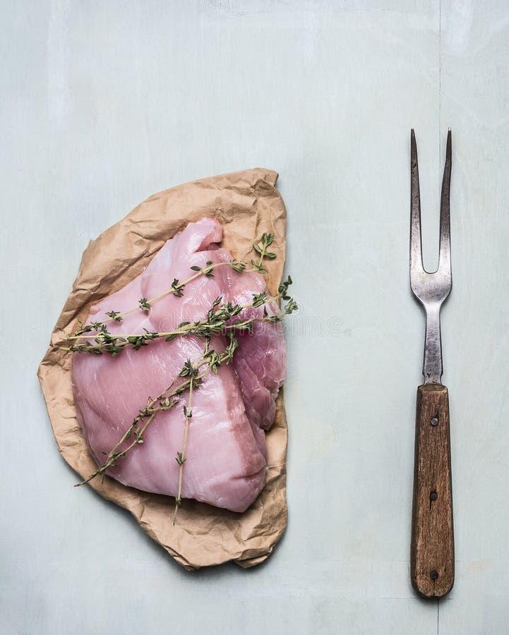 Blanc de dinde cru frais avec les herbes et le fond en bois bleu de vieille fourchette de viande, fin de vue supérieure  image libre de droits