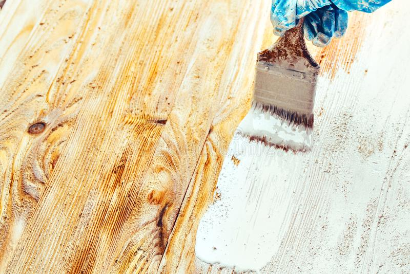 Blanc de peinture de brosse d'utilisation de main de plan rapproch? sur la surface en bois image libre de droits