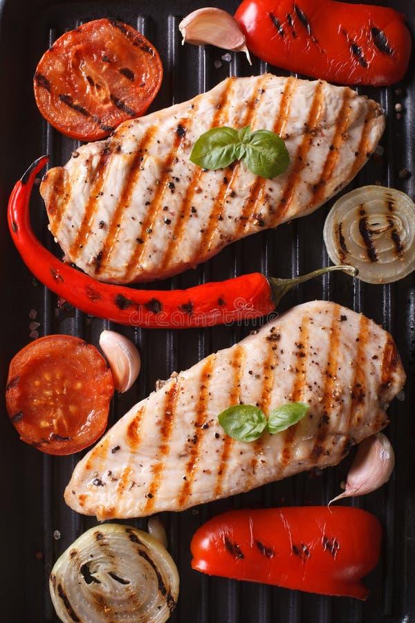 Blanc de poulet avec des légumes dans une verticale de vue supérieure de gril de casserole photos stock