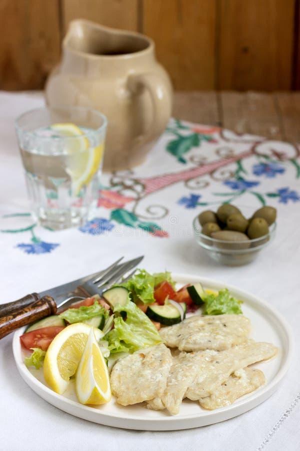 Blanc de poulet avec de la crème du lait et du citron, servie avec de la salade des légumes frais photo libre de droits