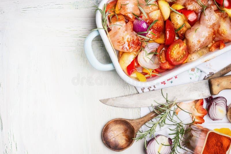 Blanc de poulet avec les légumes colorés de coupe dans la cocotte en terre émaux avec la cuillère et le couteau de cuisine en boi photo libre de droits