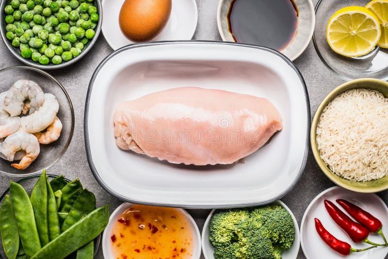 Blanc de poulet cru avec faire cuire des ingrédients : riz, légumes, épices, sauce de soja, crevettes et oeuf photos libres de droits