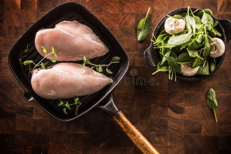 Blanc de poulet cru sur des herbes épinards et champignons de casserole de gril photographie stock
