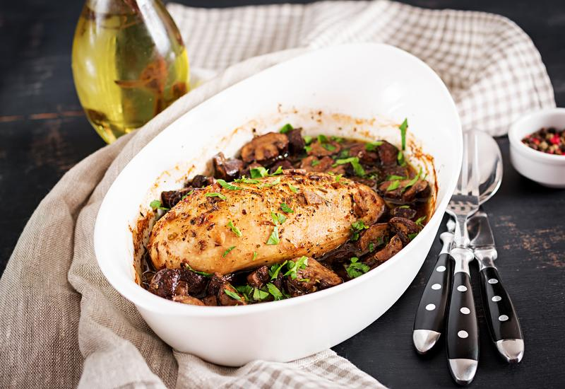 Blanc de poulet cuit au four avec des champignons en sauce balsamique sur le blanc de poulet tableBaked avec des champignons en s images libres de droits