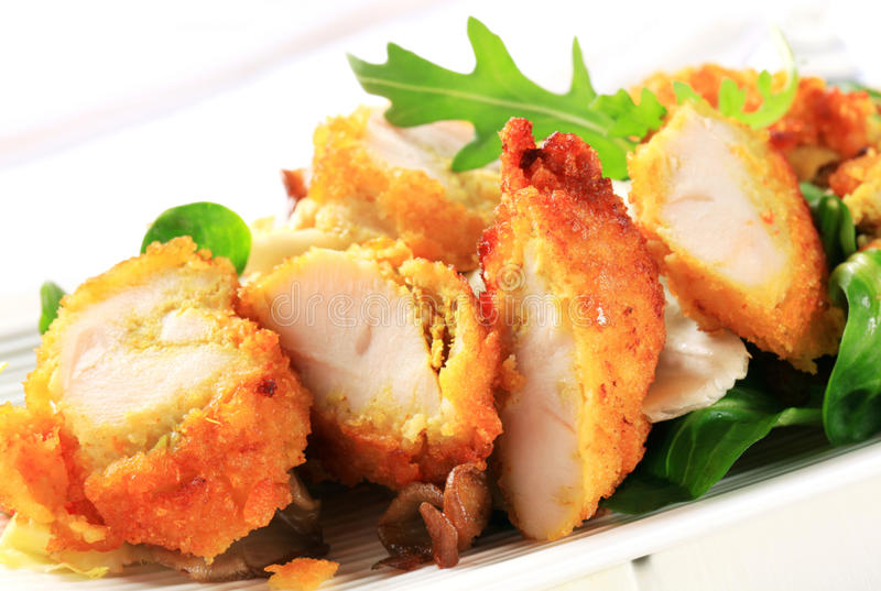 Blanc de poulet pané avec des verts de salade image stock