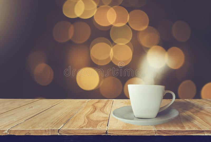 Blanc de tasse de café placé sur la table en bois avec de la fumée avec le fond de nuit, bokeh d'or lumineux, scintillant avec la photographie stock
