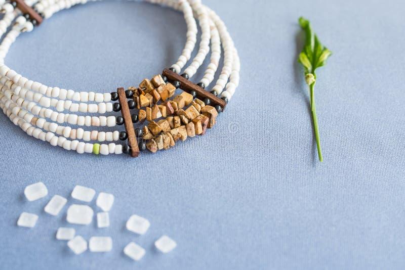 Blanc et collier en pierre de perles de tigre sur un fond bleu avec du sucre raffiné et la plante image libre de droits