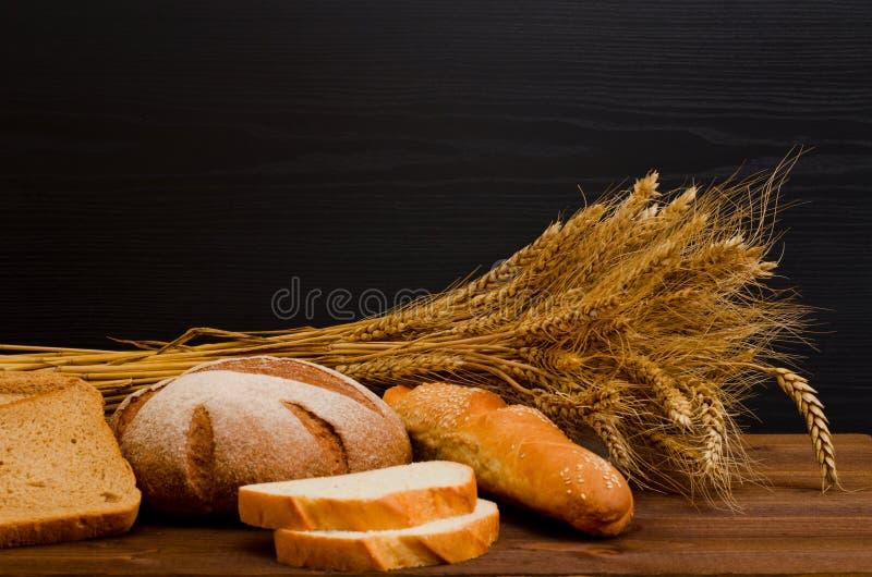 Blanc et pain de seigle, un pain, une gerbe sur la table en bois, fond noir photographie stock