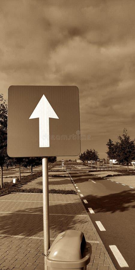 Blanc flèche poteau de signalisation dans une sépia de parking image libre de droits