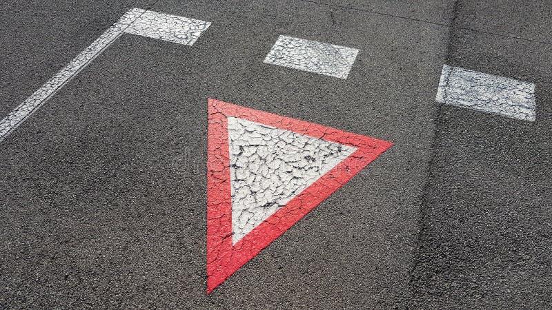 Blanc inversé avec le rendement triangulaire de panneau routier de frontière rouge du lequel vous avez besoin pour attendre photographie stock libre de droits