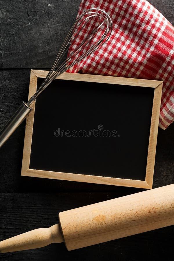 Blanc, tableau vide et noir avec la goupille en bois, batteur de fil et configuration plate à carreaux rouge de serviette de plat photos stock