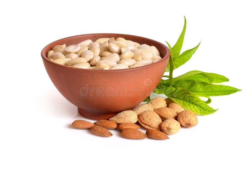 Blanched almonds In a bowl with unshelled nuts. On white background. royalty free stock image
