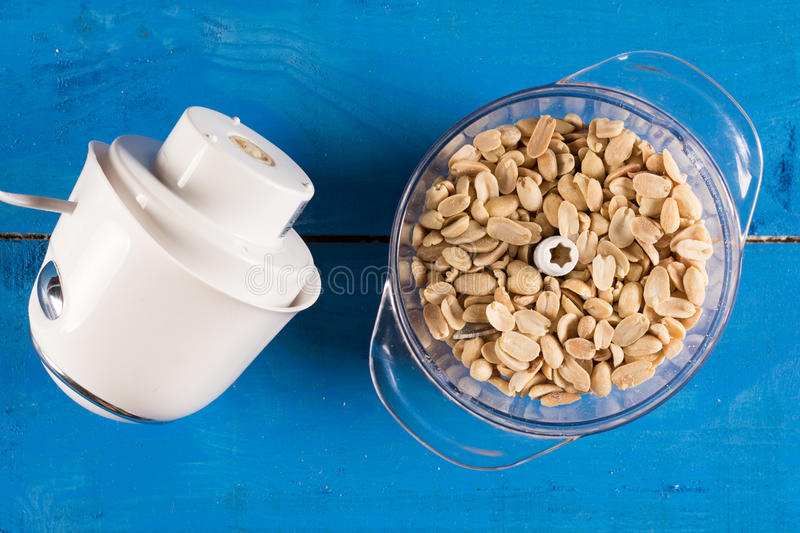 Blanched peanuts in the blender in flat lay above blue wooden ba royalty free stock photos