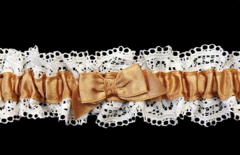 Blanching feminine garter with beige satin band. On black background royalty free stock images
