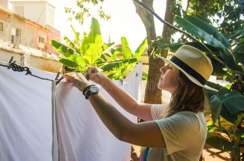 Blanchisserie accrochante de fille sur une corde à linge images libres de droits
