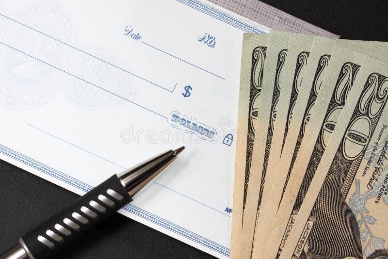 Blanco cheque met twintig dollarsrekeningen aan zijn kant stock foto's