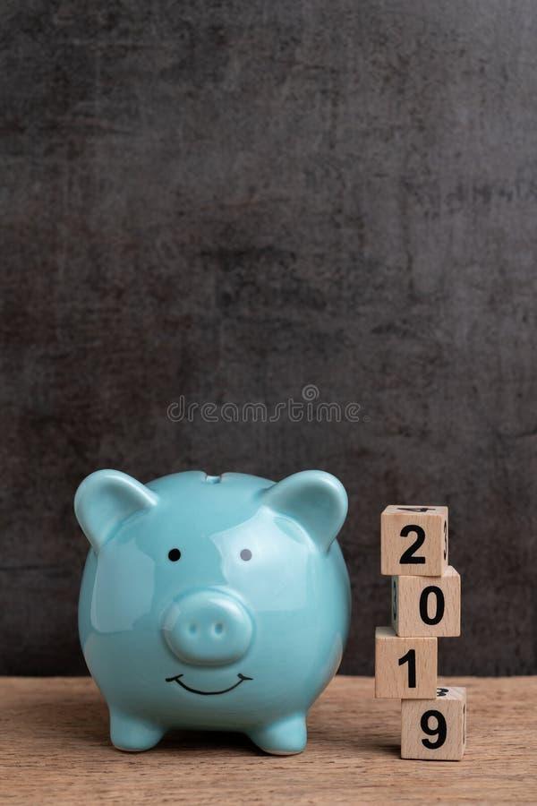 Blanco de ahorro feliz del año 2019, concepto de las metas del presupuesto, de la inversión o de las finanzas, hucha azul y pila  imagen de archivo