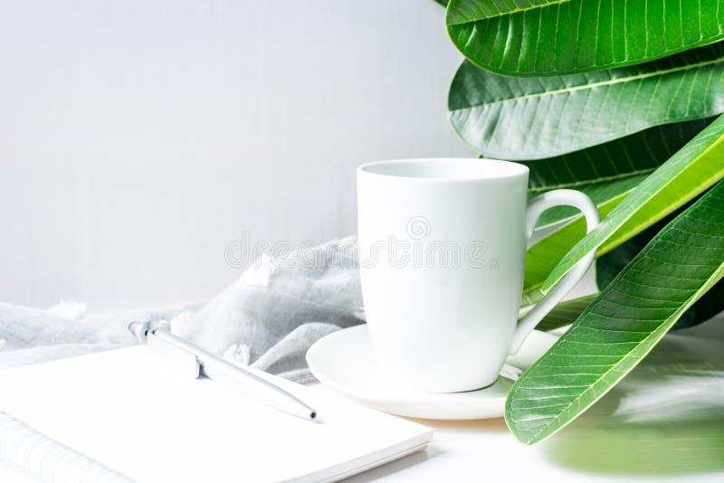 Blanco de la taza de café con las hojas y los efectos de escritorio verdes en la tabla de madera fotografía de archivo libre de regalías
