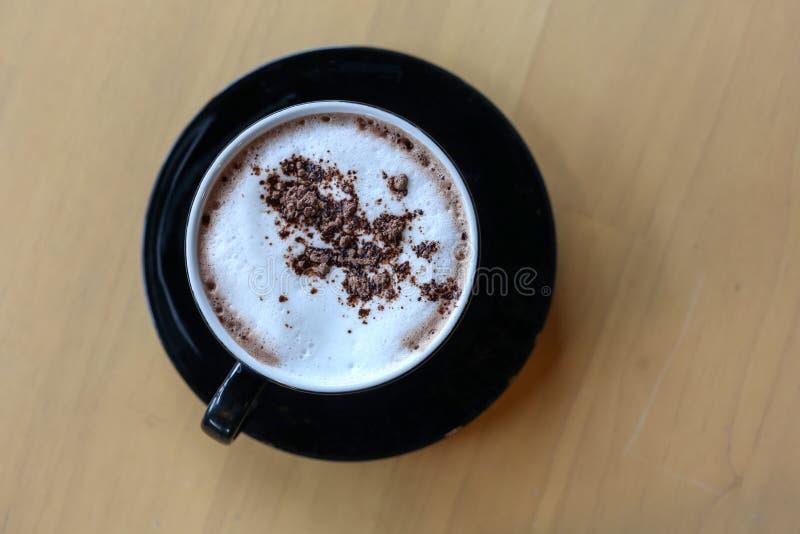 Blanco de la taza de café del alto ángulo puesto una tabla de madera en la tienda fotos de archivo