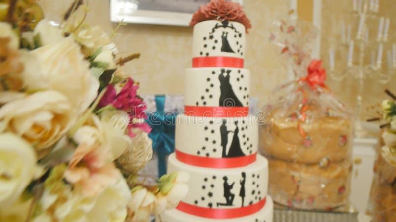 Blanco hermoso con el pastel de bodas rojo de la cinta imagenes de archivo