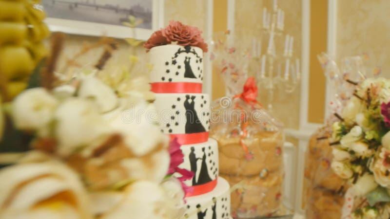 Blanco hermoso con el pastel de bodas rojo de la cinta foto de archivo