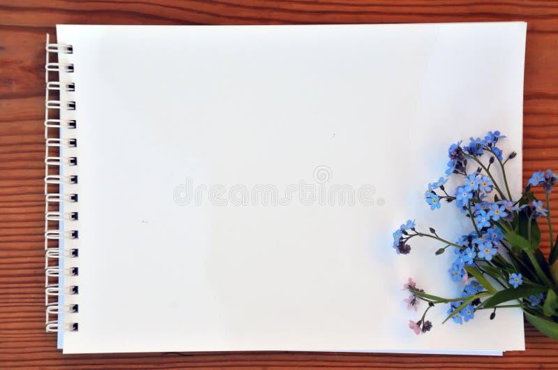 Blanco pagina van een notitieboekje en een boeket van vergeet-mij-nietjes stock foto