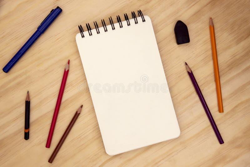 Blanco pagina van schetsstootkussen, potlood en pen op de houten mening van de lijstbovenkant Het dagboek van de de zomerreis of  royalty-vrije stock fotografie