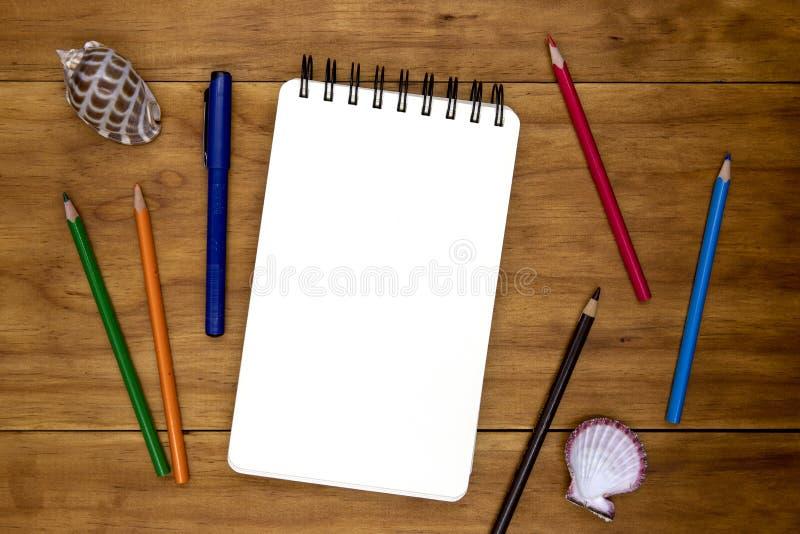 Blanco pagina van spiraalvormige blocnote op houten lijst Het kleurpotloodpotlood en de penvlakte leggen foto De lege mening van  stock afbeeldingen
