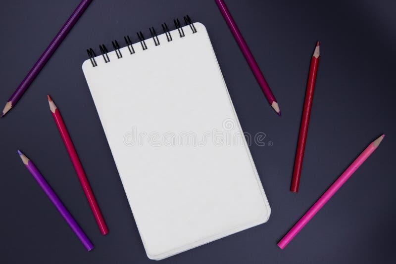 Blanco pagina van verticaal die stootkussen met roze en rood potlood op zwarte, hoogste meningsfoto schetsen De romantische achte royalty-vrije stock afbeelding