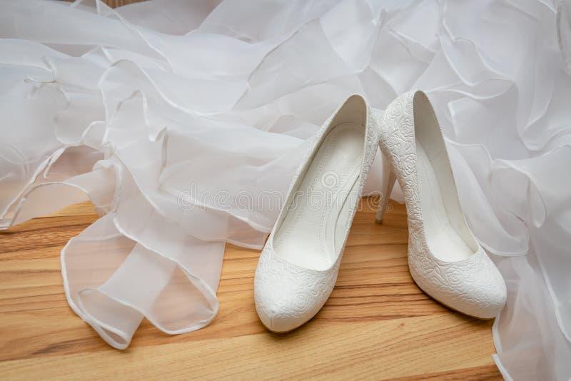 Blanco, para mujer, casandose los zapatos con los talones con los modelos en la forma de las flores en el fondo del vestido que s fotografía de archivo