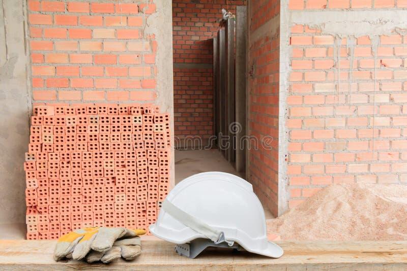 Blanco plástico del casco y construcción del equipo de cuero del guante en piso de madera Fondo de la pared de ladrillo fotos de archivo libres de regalías