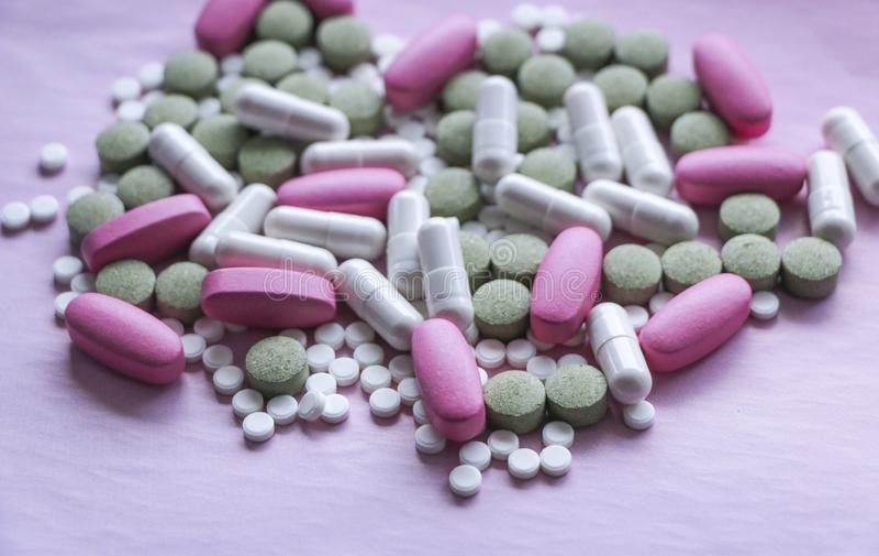 Blanco, rosa y píldoras verdes en un fondo rosado drogas multicoloras imágenes de archivo libres de regalías