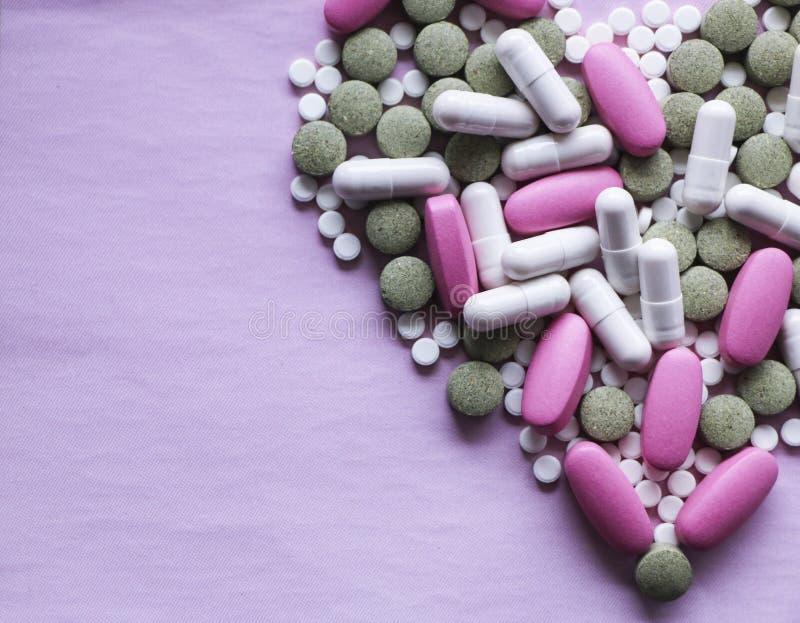 Blanco, rosa y píldoras verdes en un fondo rosado drogas multicoloras imagenes de archivo