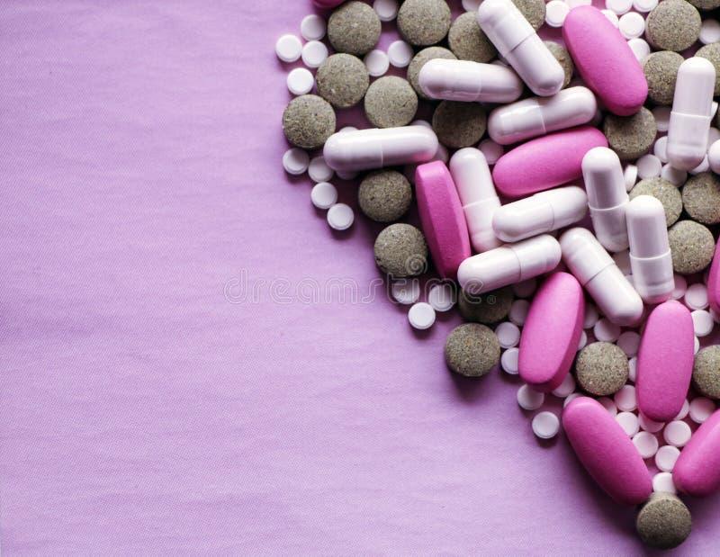 Blanco, rosa y píldoras verdes en un fondo rosado drogas multicoloras fotos de archivo