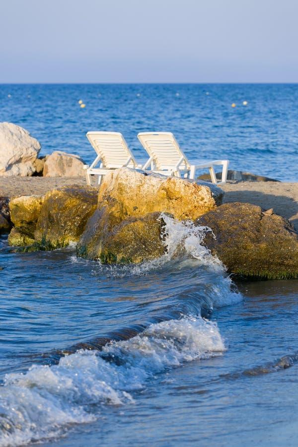 Blanco, sunbeds plásticos en la hora de oro en la playa arenosa de Zakynthos, Grecia imagen de archivo
