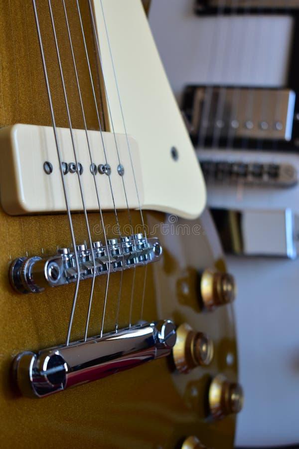 Blanco y detalles superiores de las guitarras eléctricas del oro imagenes de archivo