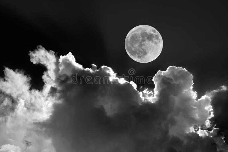 Blanco y negro de la Luna Llena en cielo nocturno con las nubes iluminadas por la luna soñadoras imagenes de archivo