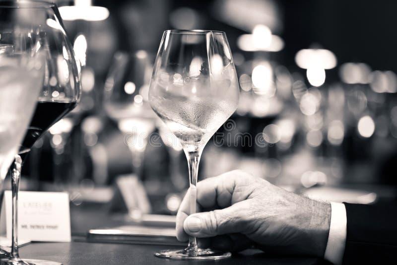 Blanco y negro del vino blanco a mano con la cena en restaurante imagenes de archivo
