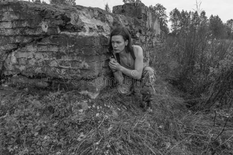 Blanco y negro, la muchacha con una pistola en las manos se encogió detrás fotos de archivo libres de regalías