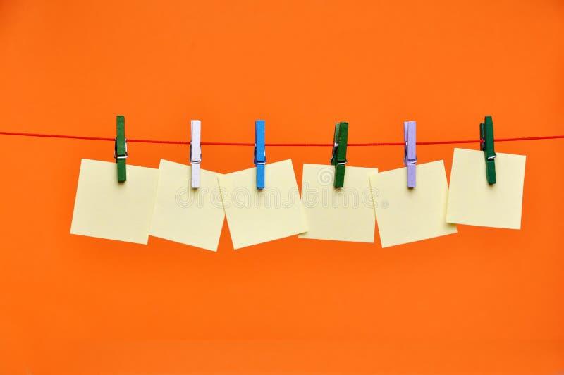 Blancs de papier s'arrêtant sur une corde images stock