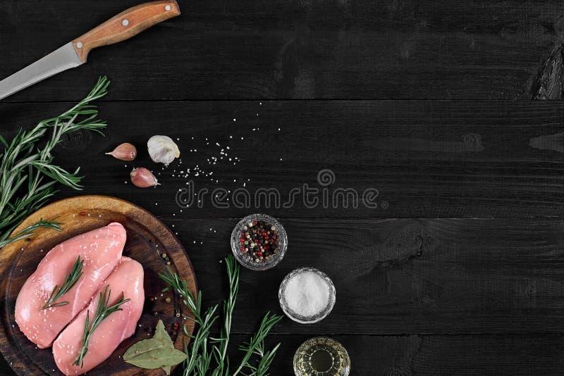 Blancs de poulet crus sur la planche à découper en bois avec des herbes et des épices Vue supérieure avec l'espace de copie images libres de droits