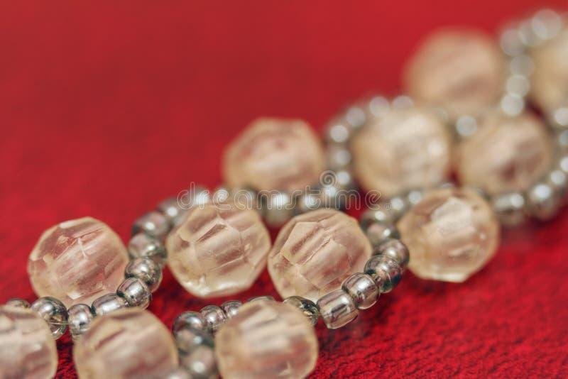 Blancs multicolores pour des perles en gros plan Macro photo sur un fond rouge image stock