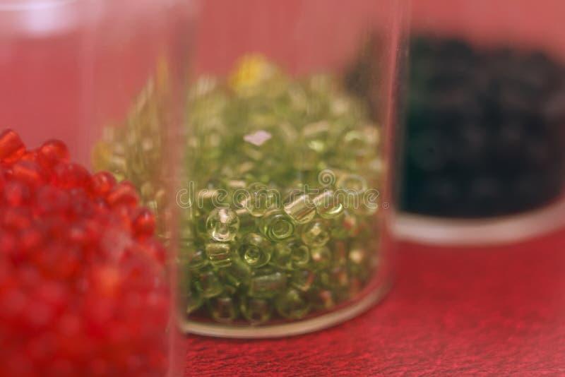 Blancs multicolores pour des perles en gros plan Macro photo sur un fond rouge images libres de droits
