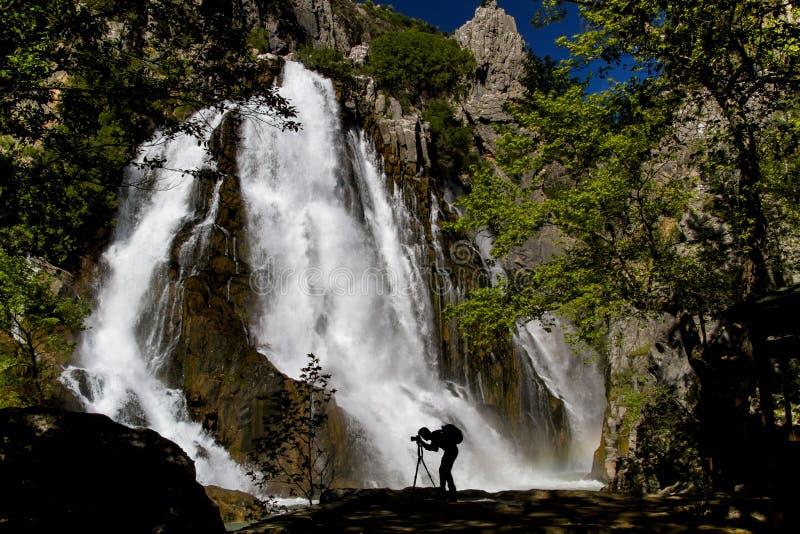 Bland bergen, den stora vattenfallet som flödar i kanjonen, sjön och fotografen som tar dem royaltyfri foto
