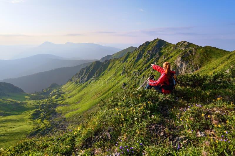 Bland de lösa bergblommorna på kanten av klippan finns det en flicka som sitter och håller ögonen på maxima av berg arkivbilder