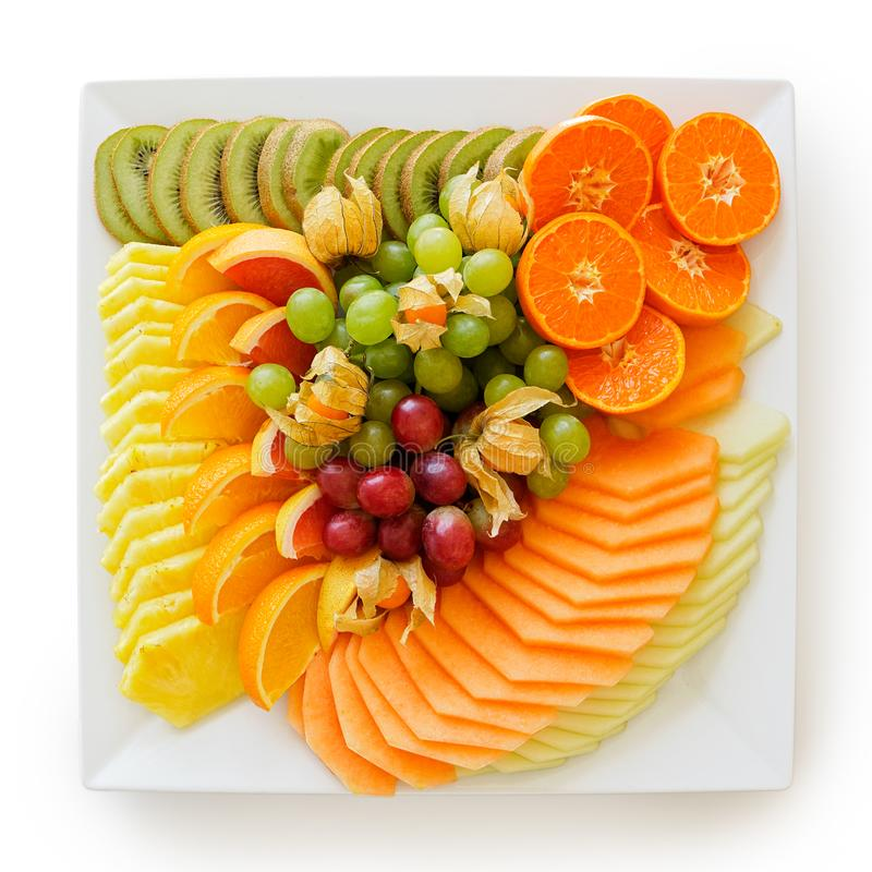 Blanda av nytt klippt tropiskt och citrusfrukt som ordnas på det vita fyrkantiga keramiska uppläggningsfatet på vitt från över royaltyfria bilder