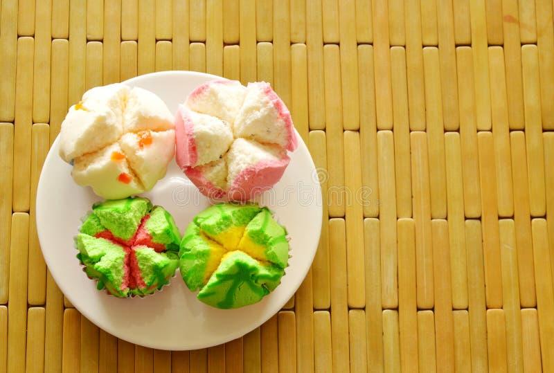 Blandad färgrik bomullkaka i pappers- kopp på maträtt royaltyfria foton